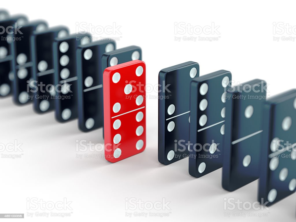 Red domino tile among black ones stock photo