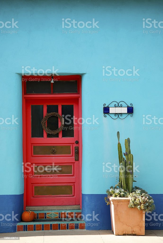 Red Door and Cactus Against Blue Stucco Wall royalty-free stock photo