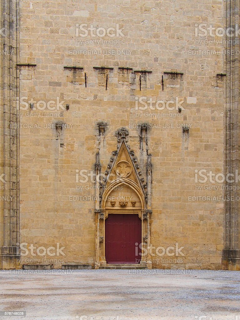 Red door of the cathedral of Narbonne, in spring stock photo