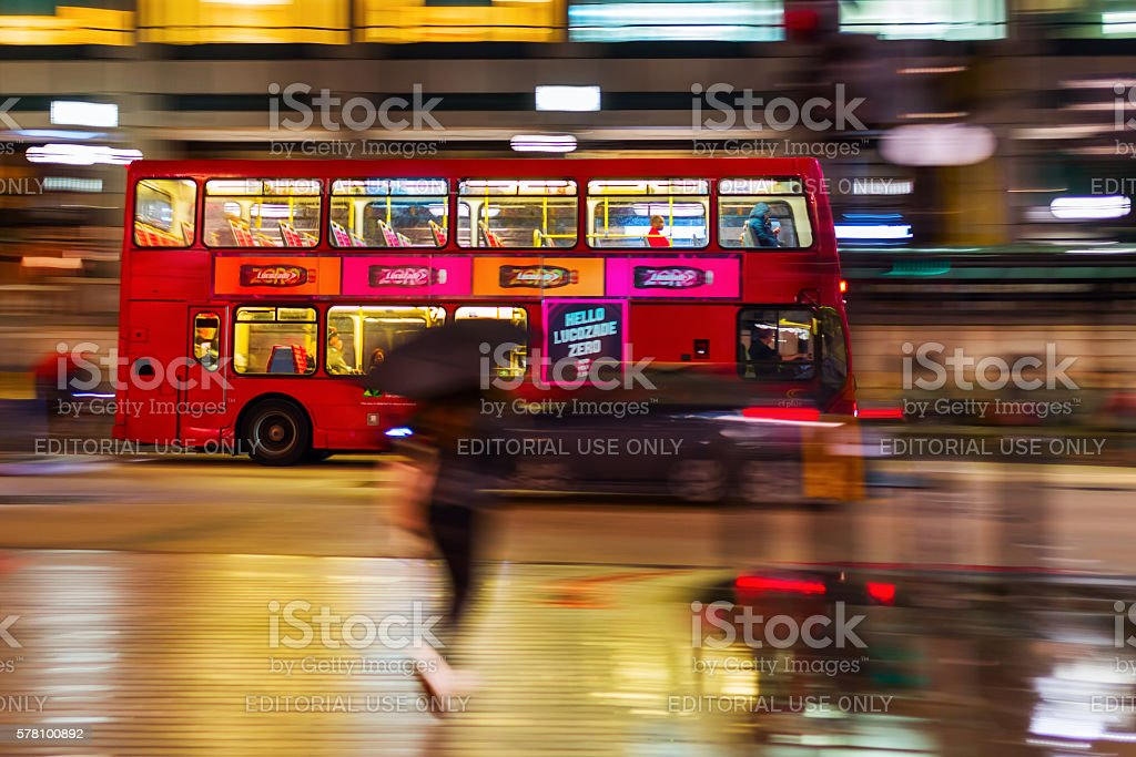 red double decker bus at night in London, UK stock photo