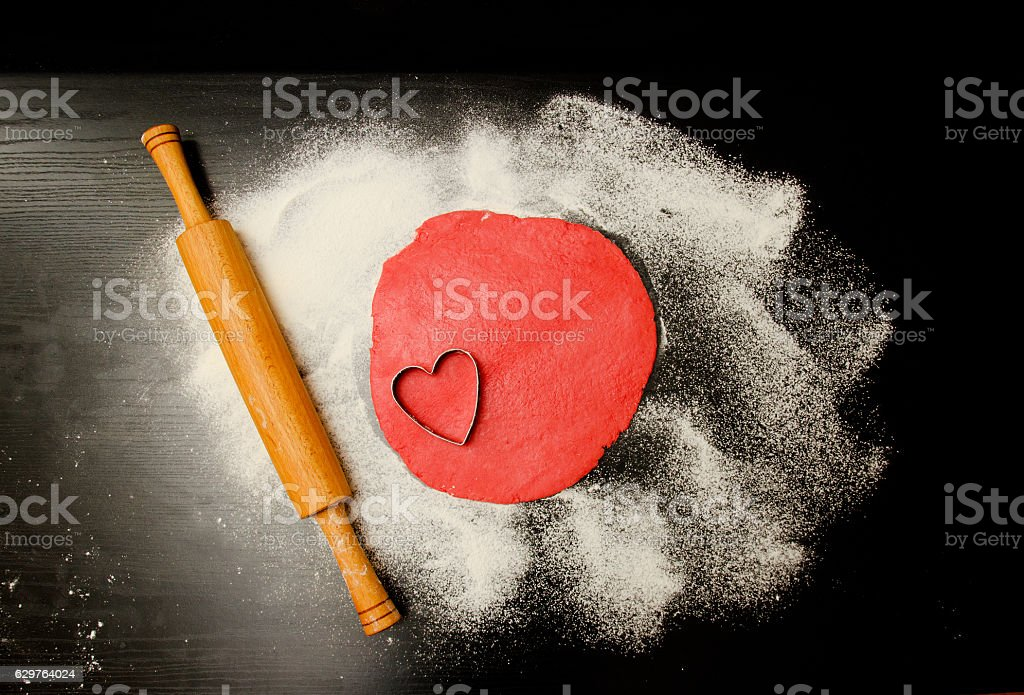 Red dough to form cut-out hearts on black table stock photo