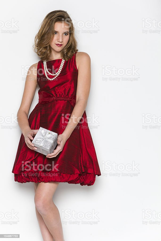 red dress teen girl holding christmas present stock photo
