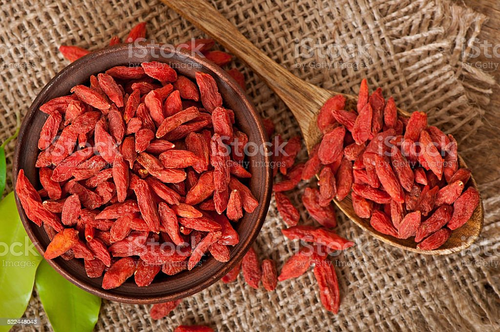 Red dried goji berries in wooden spoon stock photo