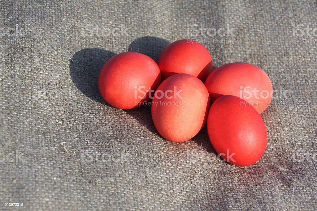 Red Easter eggs on a brown napkin outdoors stock photo