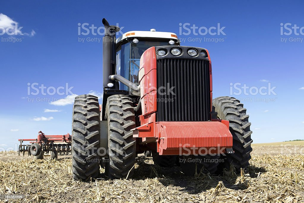 Red Eight Tire Tractor in Harvested Field stock photo