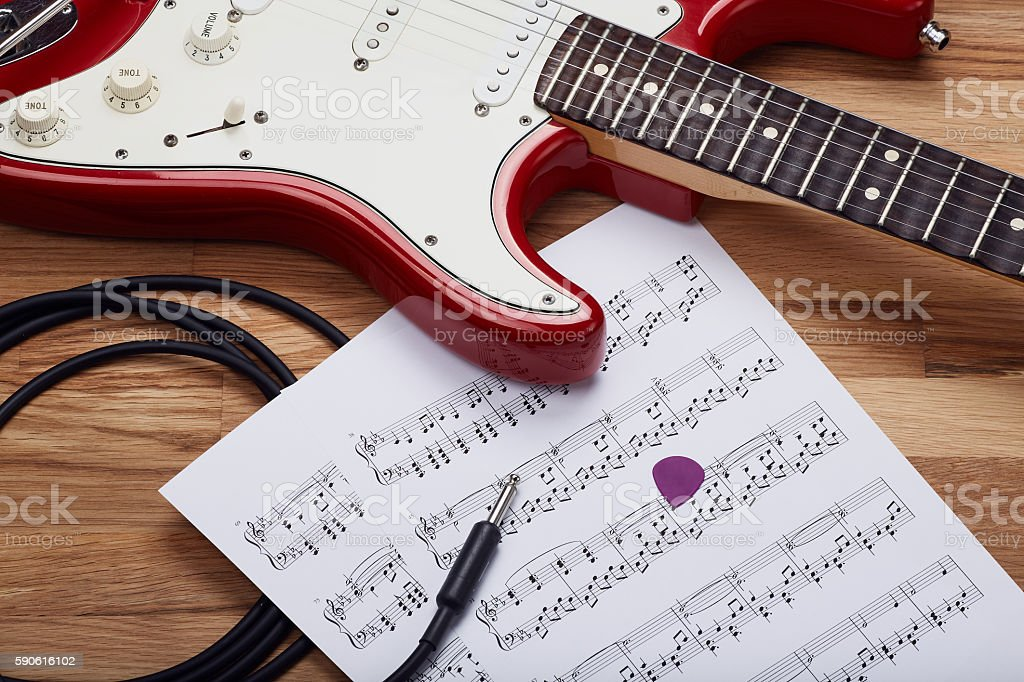 Red electric rock guitar with sheet music stock photo