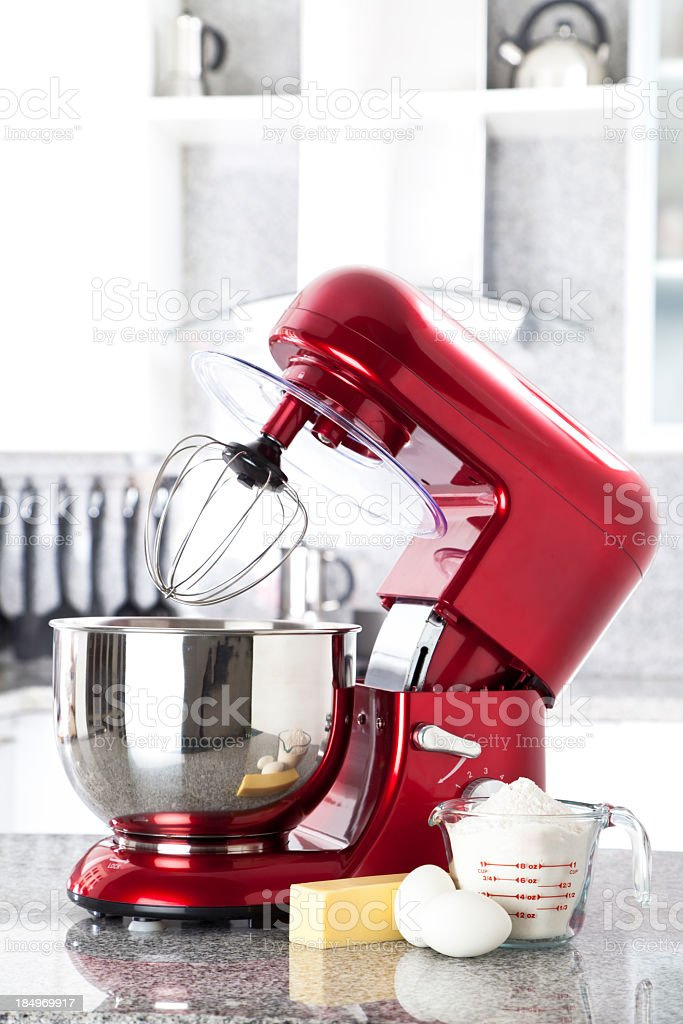 Red electric stand mixer on kitchen counter top stock photo