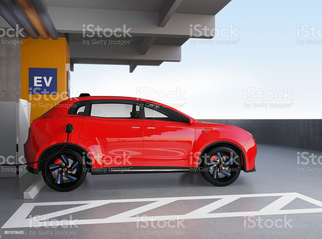 Red electric SUV recharging in parking garage stock photo