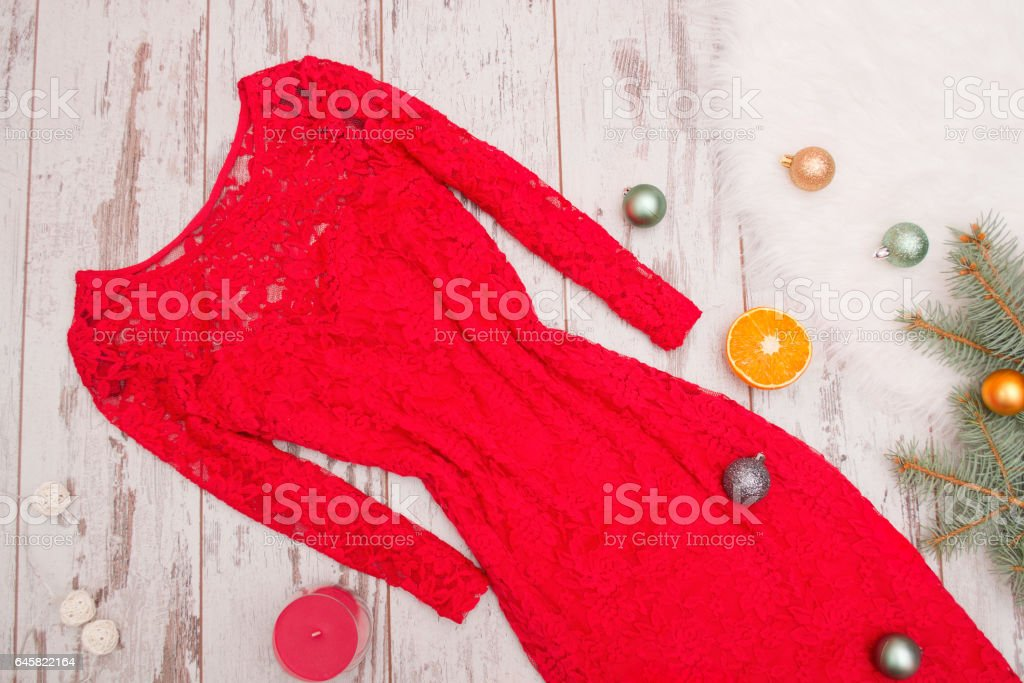 Red elegant lace dress on a wooden background, spruce branch, balls, candle, orange. Fashion concept. Close-up stock photo