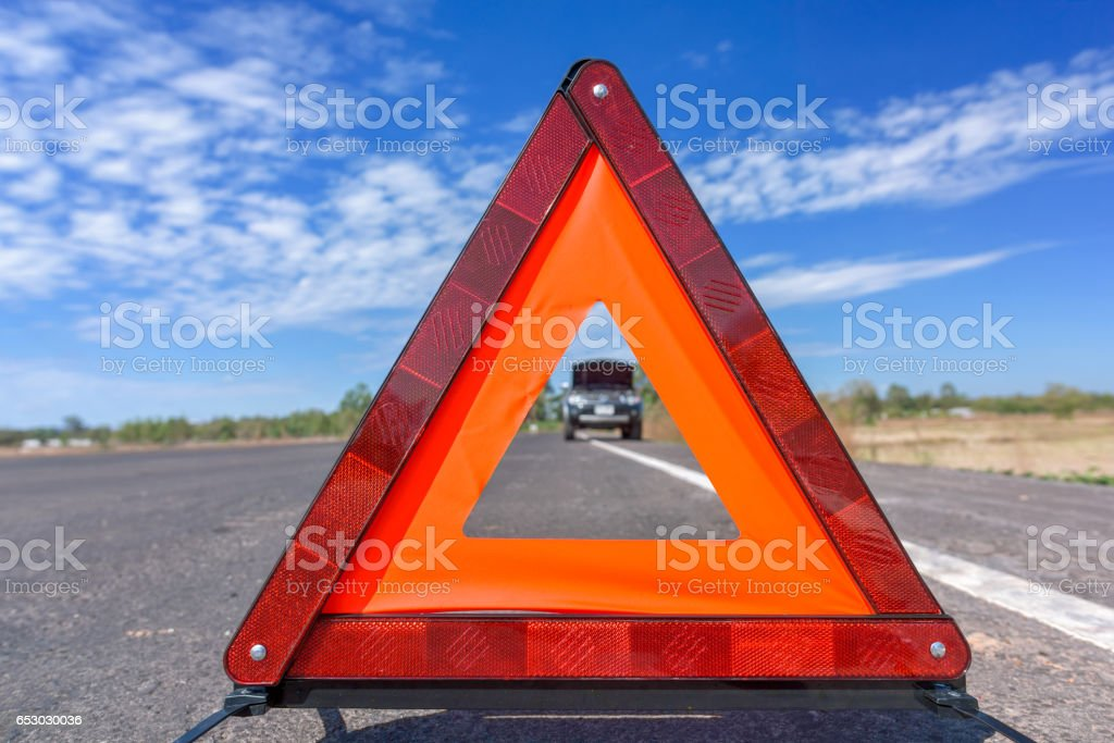 Red emergency stop sign and broken car on the road stock photo