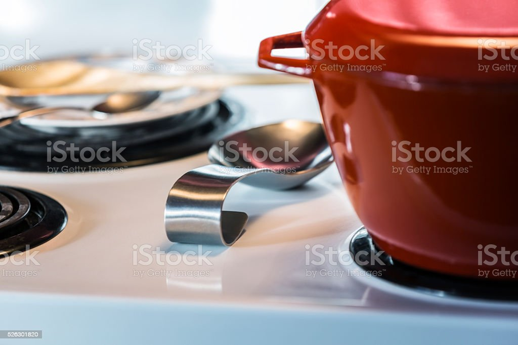 Red Enamel Cooking Pot Close-Up On Kitchen Electric Stovetop stock photo