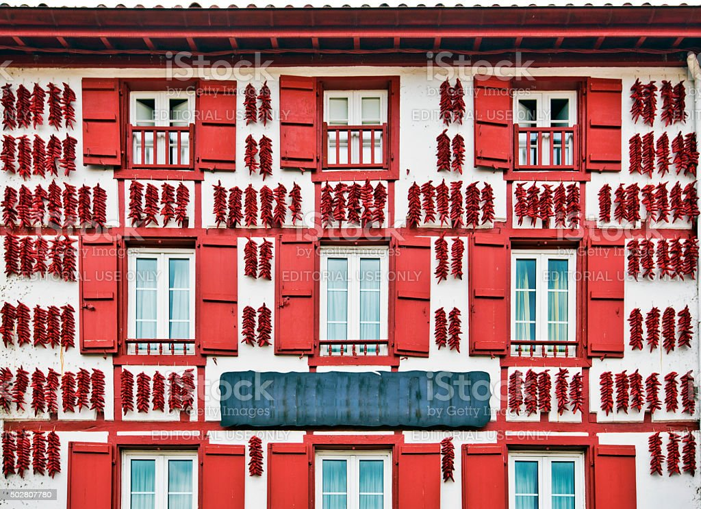 Red Espelette peppers drying in the wall of Basque house stock photo