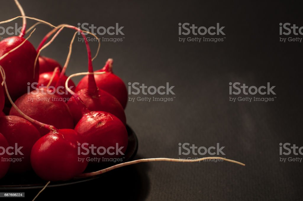 Red european radishes / Red radish / Red natural european radishes on a black background stock photo