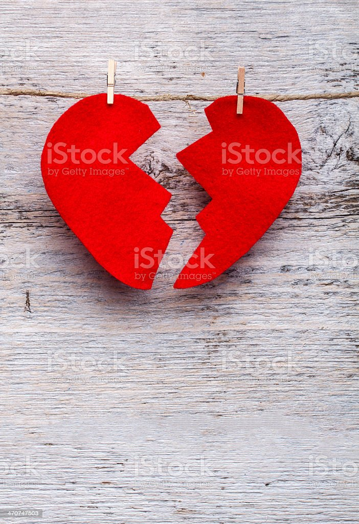 Red felt heart cracked in two on pegged to twine stock photo