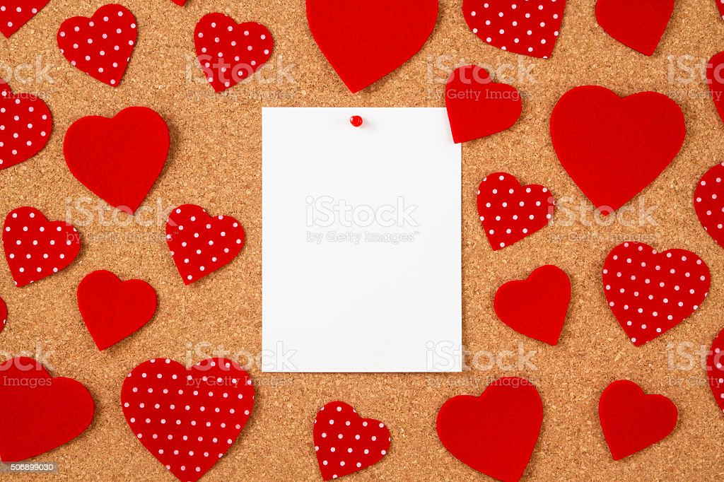 Red Felt Hearts and White Paper Pinned on Cork Background stock photo