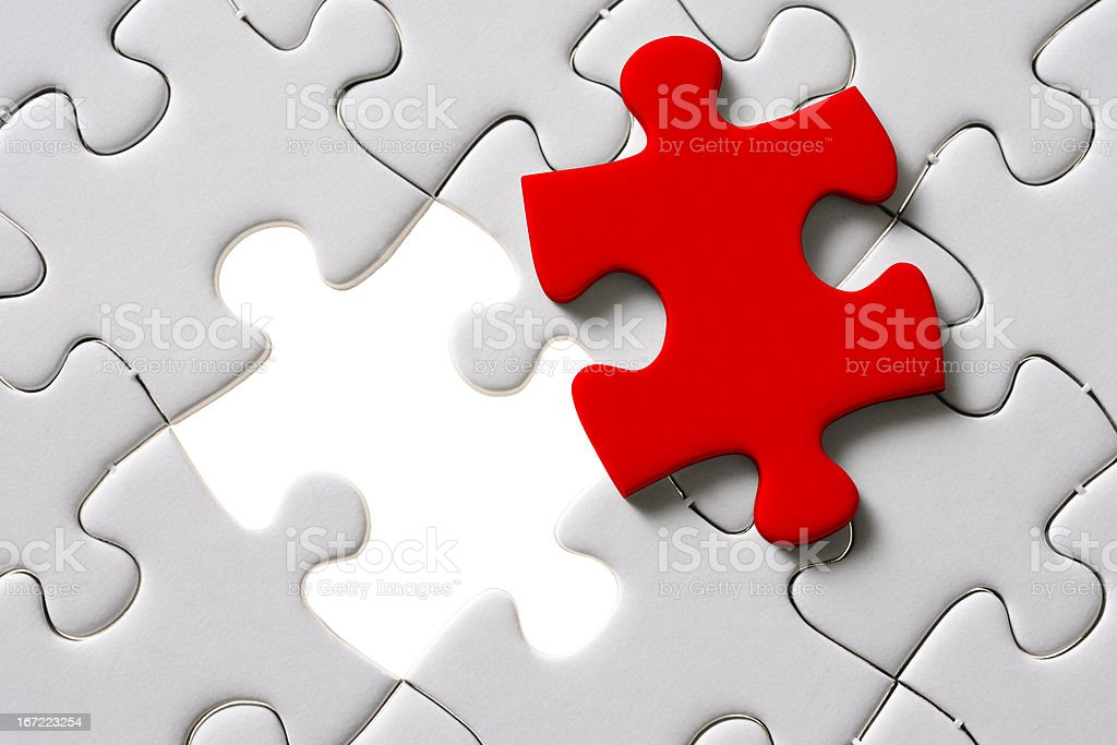 Red final piece of the jigsaw with light from behind royalty-free stock photo