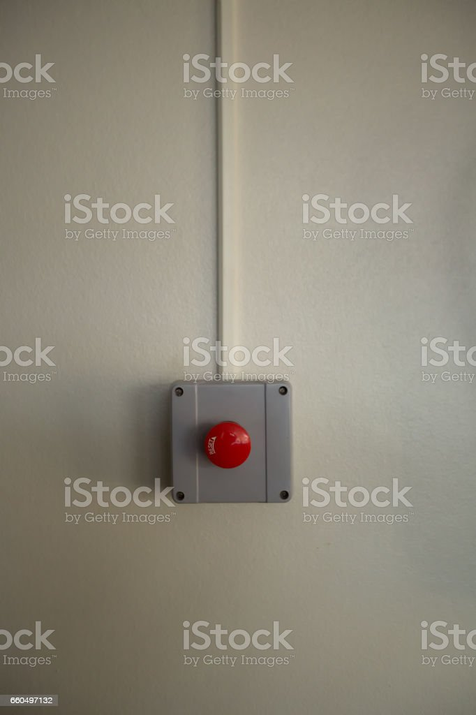 Red fire alarm switch at cement wall stock photo