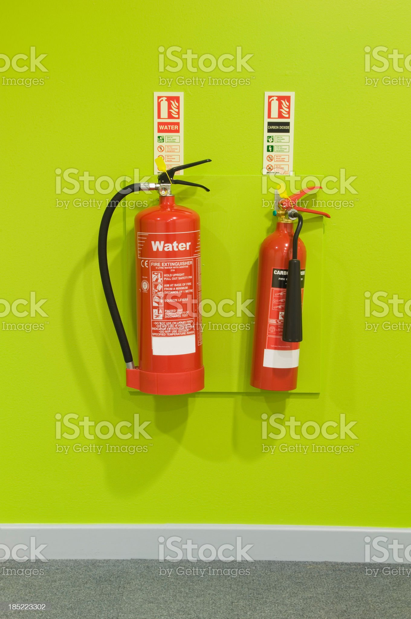Red fire extinguishers on a green wall royalty-free stock photo