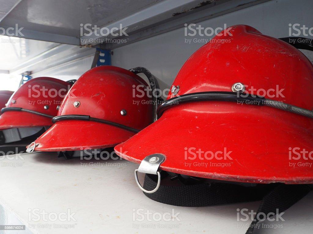 Red fireman helmet prepared on shelf. stock photo
