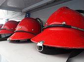 Red fireman helmet prepared on shelf.