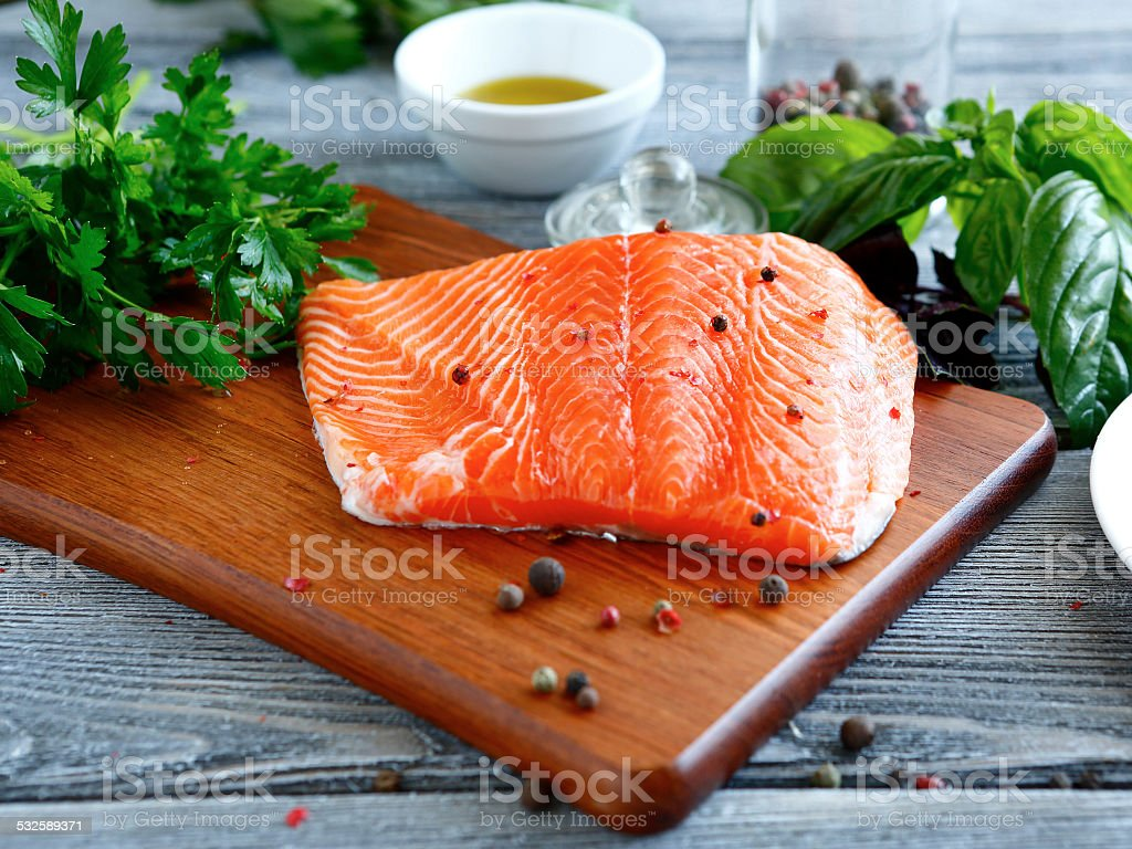 Red fish fillet with parsley, pepper and basil stock photo