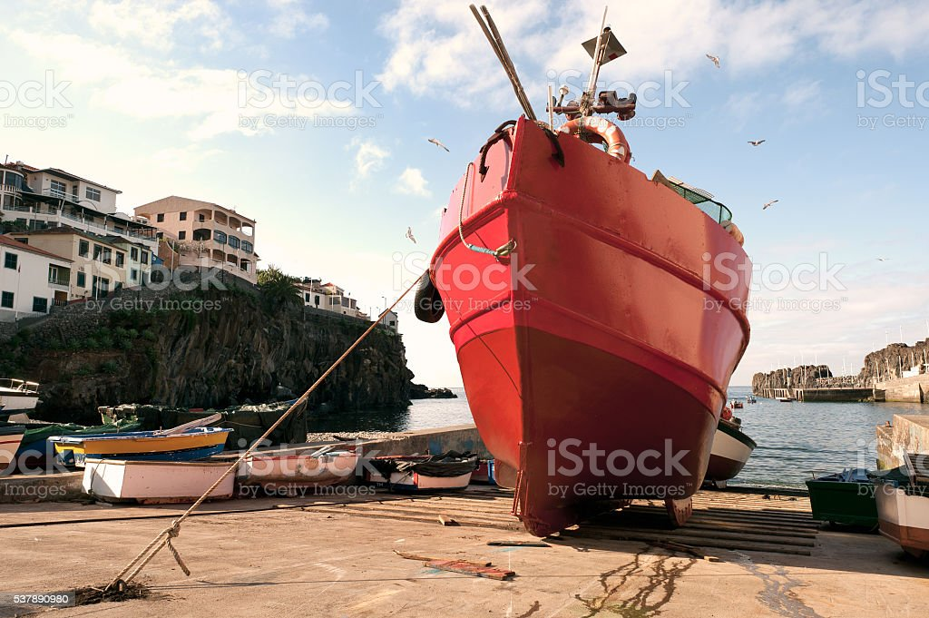 Red fishing boat in dry dock surrounded by sea gulls stock photo
