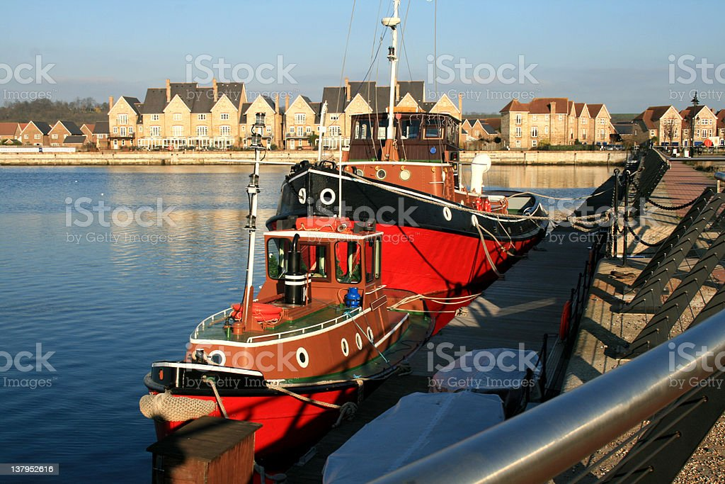 Red fishing boat in the water with houses in the background stock photo