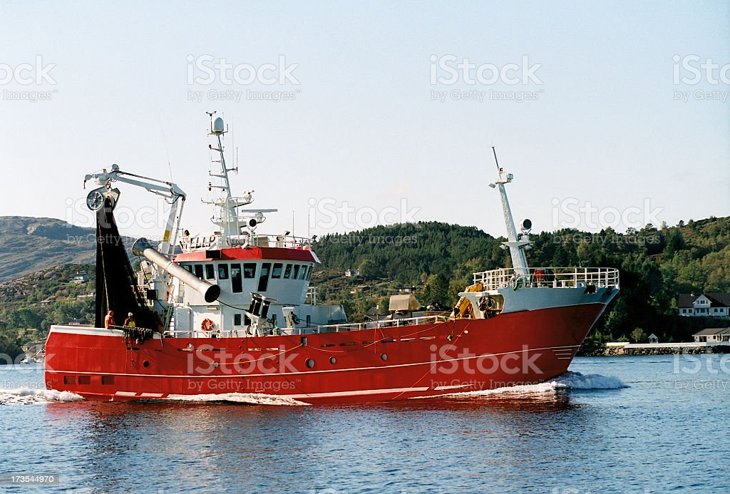 A red fishing trawler moving out of the bay royalty-free stock photo