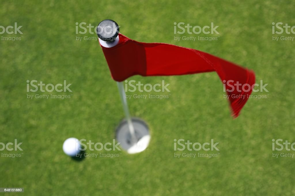 Overhead shot of red flag and golf balls on putting green.
