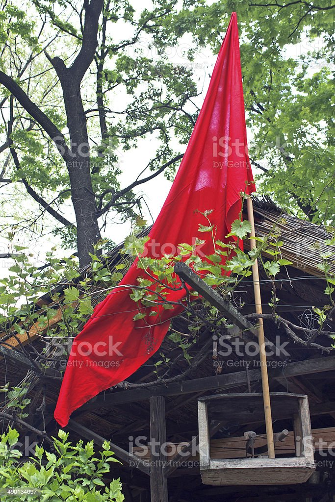 Red flag on cottage  in forest royalty-free stock photo