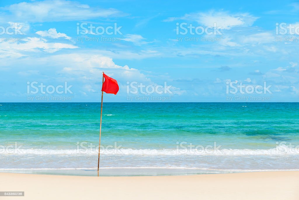 Red flag on tropical beach stock photo