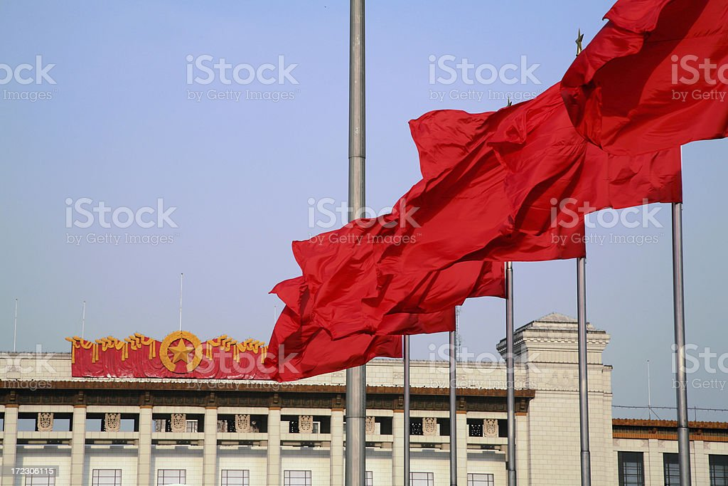 Red flags in front of the communist party emblem stock photo
