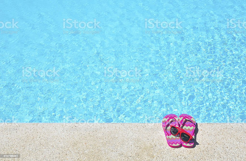 Red flip-flops and sunglasses beside the blue pool stock photo