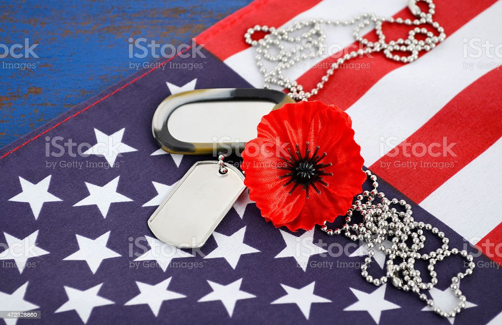 Red flower and soldier tags over an US Flag for Memorial Day stock photo