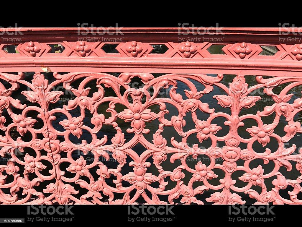 red flowers cast iron on bridge railing stock photo