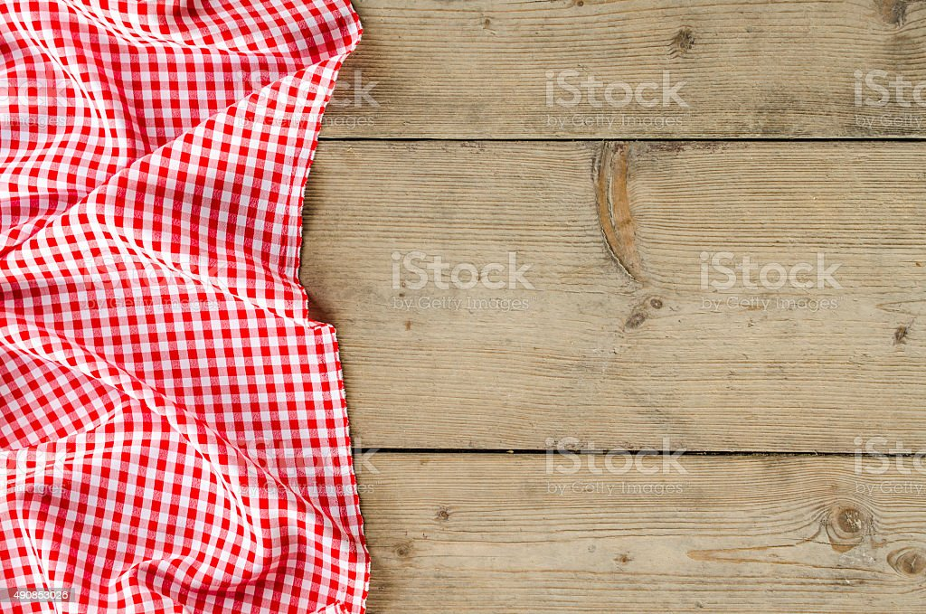 Red folded tablecloth over wooden table stock photo