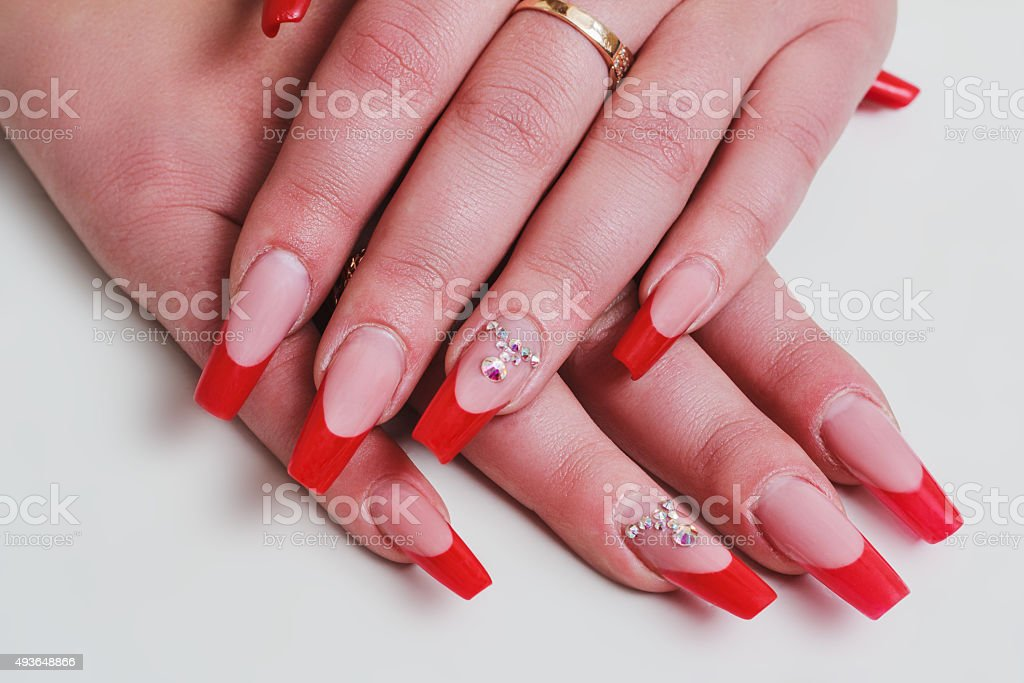 Red french nail art with rhinestones stock photo
