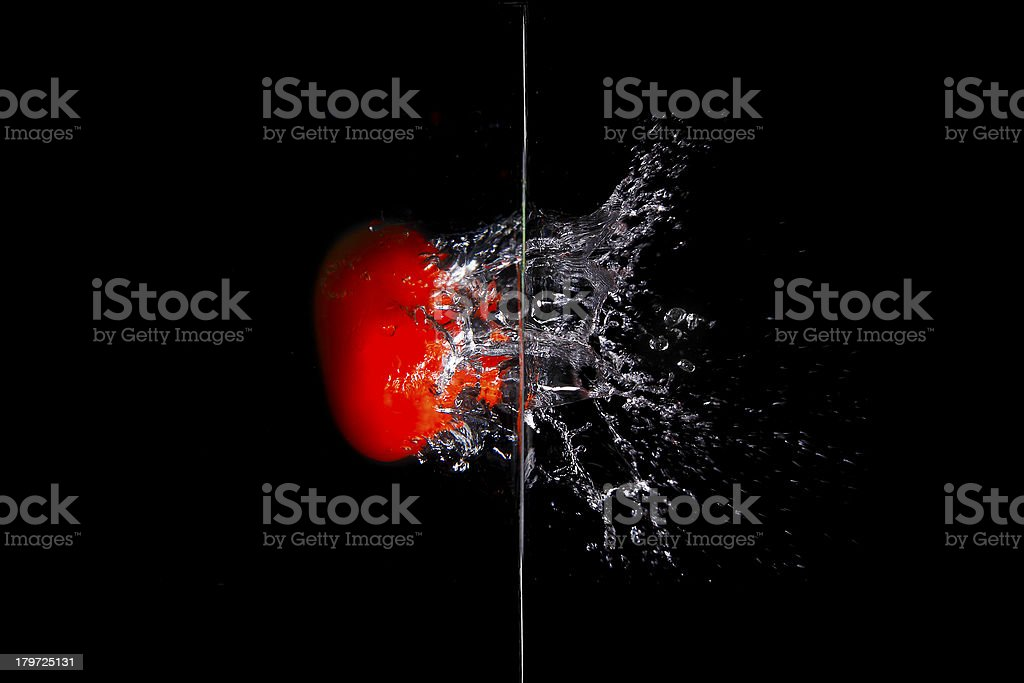 Red fruit dropped into water with splash isolated on black royalty-free stock photo