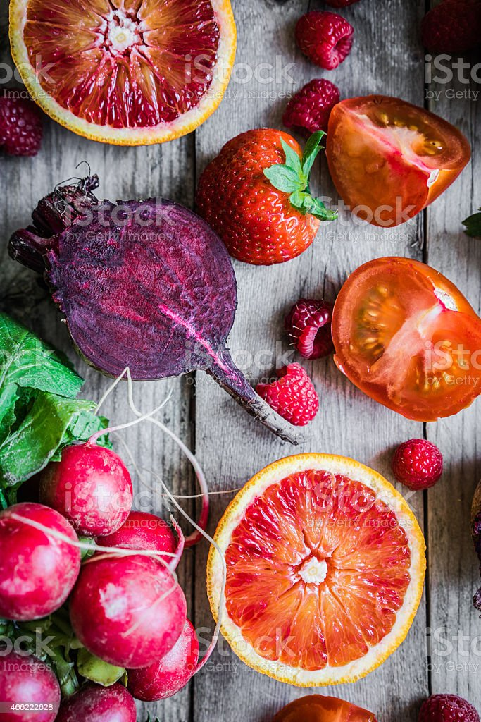 Red fruits and vegetables on wooden background stock photo