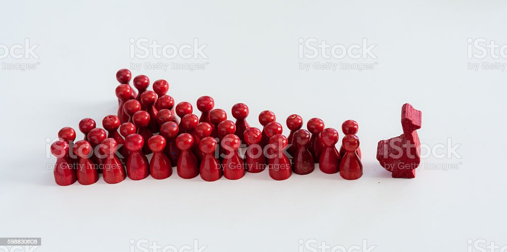 Red game pawns follow a red duck or goose stock photo