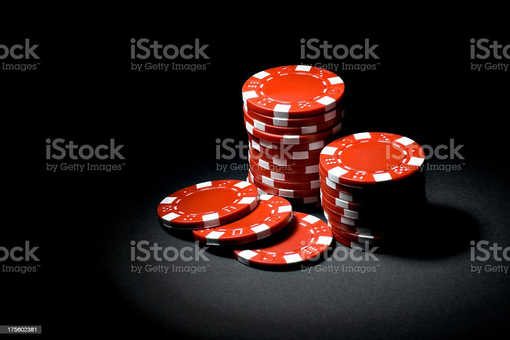 Red gaming chips in a spotlight on black background stock photo