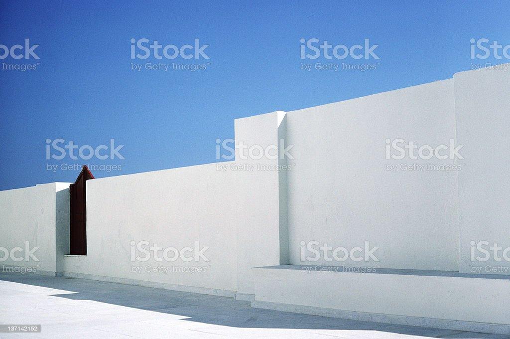 Red Gate, White Wall, Blue Sky, Oia, Santorini, Greece royalty-free stock photo