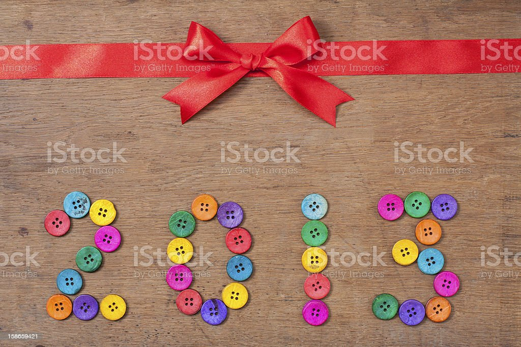 Red gift bow, New Year 2013 date on wooden background royalty-free stock photo