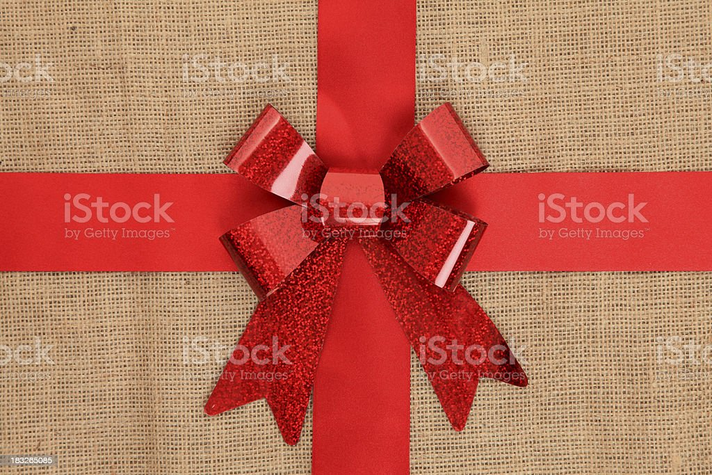 Red gift bow on hessian background stock photo