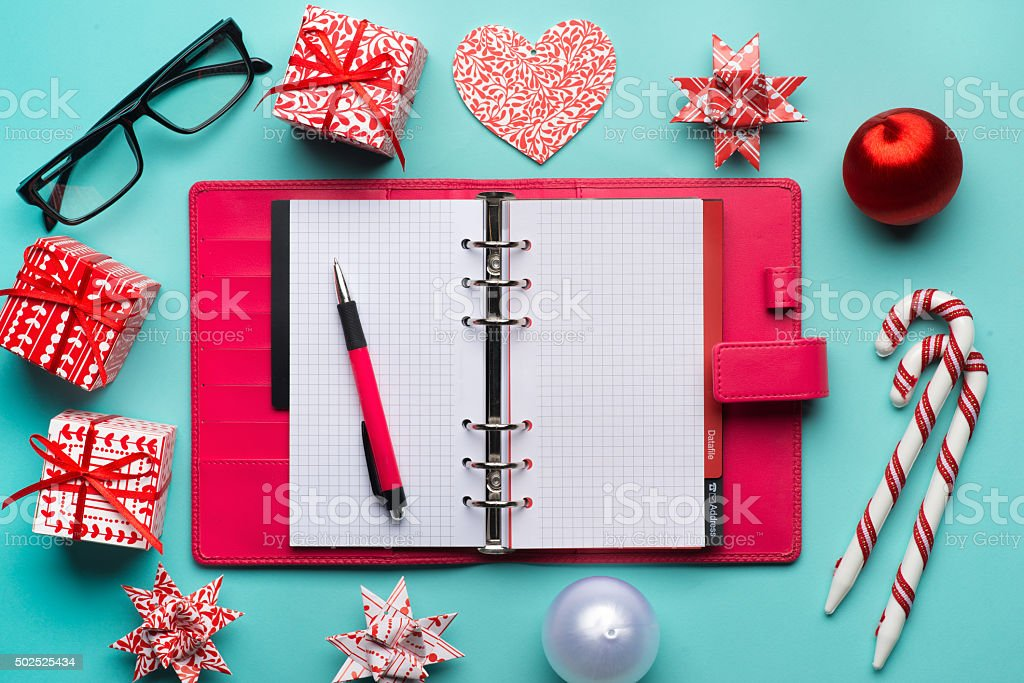 Red gift box and colorful diary over cyan background stock photo