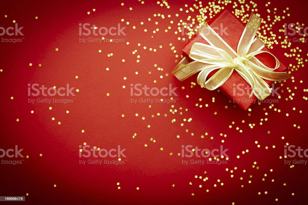 Red gift box in gold bow on red background with gold glitter royalty-free stock photo