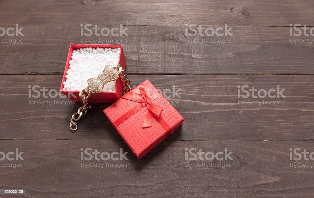 Red gift box is on the wooden background stock photo