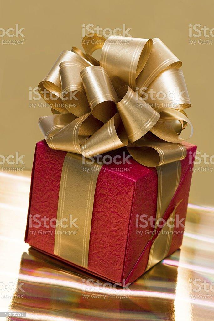 Caixa de presente vermelha na bsckground dourada foto de stock royalty-free