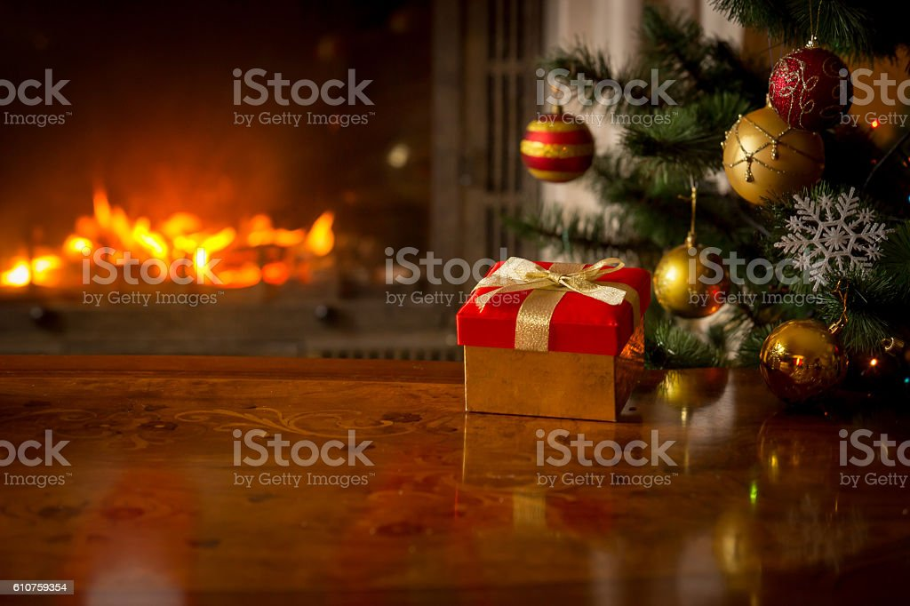 Red gift box on table in front of fireplace stock photo