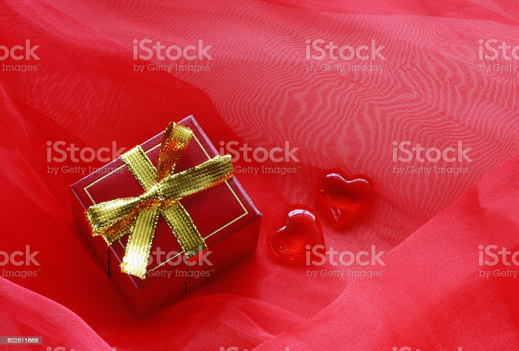 red gift box with gold ribbon and hearts stock photo